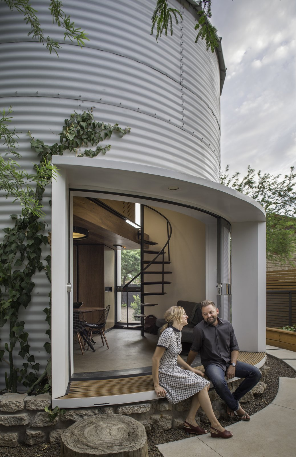 "Outdoor, Gardens, Side Yard, Wood, Walkways, Back Yard, Horizontal, Concrete, and Hanging Christoph Kaiser, principal at Kaiserworks, reimagined a 1955 grain silo as a 340-square-foot home in Phoenix, Arizona. The corrugated, steel-clad house is 18 feet in diameter and features a 26-foot-high ceiling and a 17-foot operable slot window that fames views of the city. While the exterior displays a wonderfully industrial aesthetic, the interior is surprisingly cozy. ""I wanted a warm interior, almost if you designed Wurlitzer to tend to all human needs and then slid it into one cylinder,"" says Kaiser, who employed built-in furniture, a spiral staircase, and a mezzanine bedroom with an in-wall projector for the ideal movie-watching experience.  Outdoor Side Yard Concrete Walkways Gardens Photos from An Old Grain Silo Makes an Enchanting Tiny Home in Phoenix"