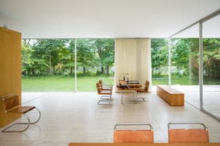 Inside the Farnsworth House, an eight-inch gap lines the perimeter and keeps condensation at bay. The area pictured between the desk and the dining table serves as the entry.