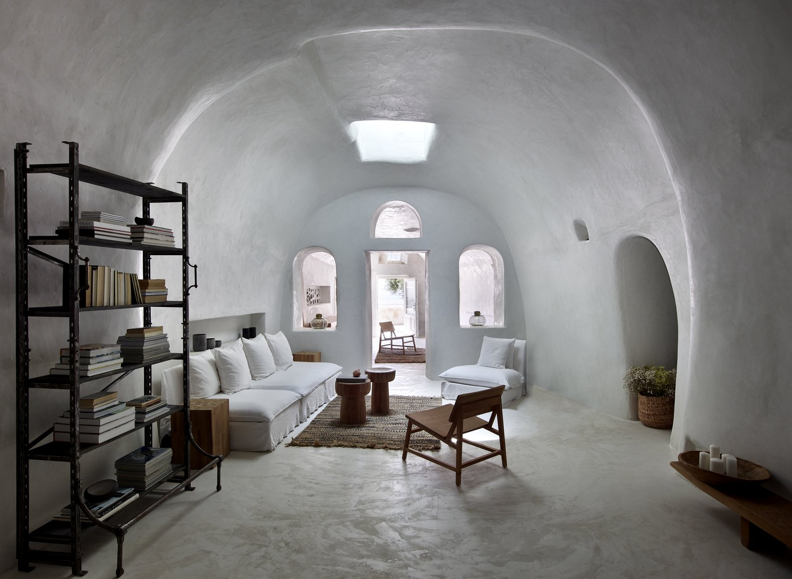 Living Room, Chair, Sofa, End Tables, and Bookcase For his own home nearby, Bellonias transformed a cave dwelling into a three-bedroom getaway featuring pressed cement walls and skylights that bring light into the serene interiors.   Photo 2 of 10 in These Dreamy Villas on Santorini Take Inspiration From Traditional Cave Dwellings