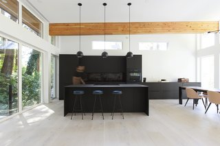 MIZA Architects completely renovated the Capilano Crescent Residence. Nestled in the trees, the home is filled with light and plenty of space. The black kitchen offers a contemporary contrast to the white walls and light hardwood floors.