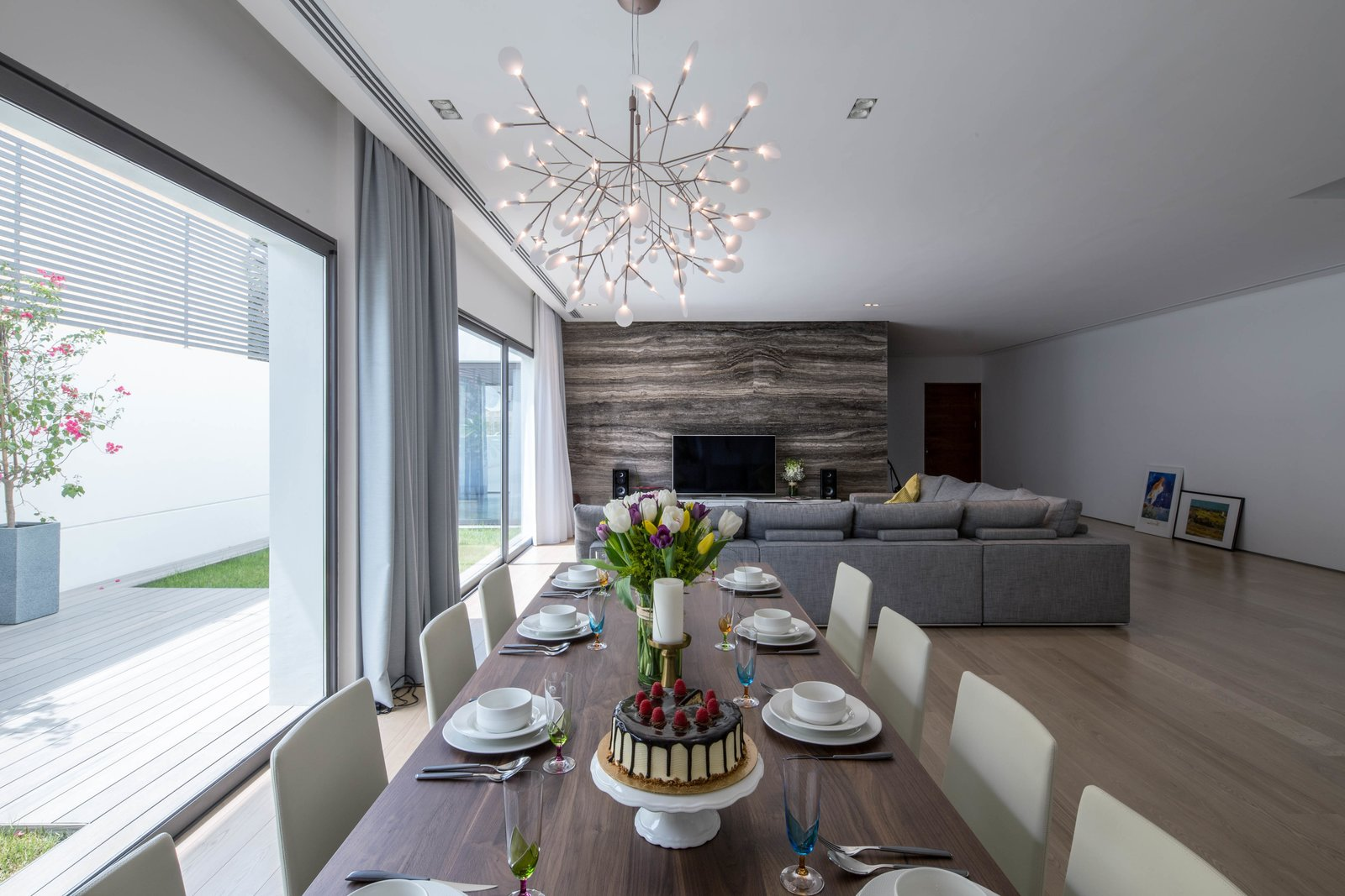 Dining Room, Chair, Table, Light Hardwood Floor, Lamps, Ceiling Lighting, Pendant Lighting, and Travertine Floor Living room and dining area looking over the private garden  A House in Yarmouk by Studio Toggle