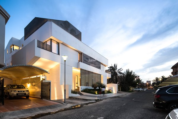 Outdoor, Trees, Shrubs, Grass, Raised Planters, Gardens, Garden, Concrete Patio, Porch, Deck, Front Yard, Stone Patio, Porch, Deck, Horizontal Fences, Wall, Metal Patio, Porch, Deck, Metal Fences, Wall, and Landscape Lighting Street view, dusk  A House in Yarmouk by Studio Toggle
