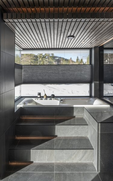 The spa-like bathroom of Casa Myhrer Hauge offers sweeping views of the surrounding landscape. Gudmundur Jonsson Arkitektkontor wanted the design to play off of nature, not encroach on it.