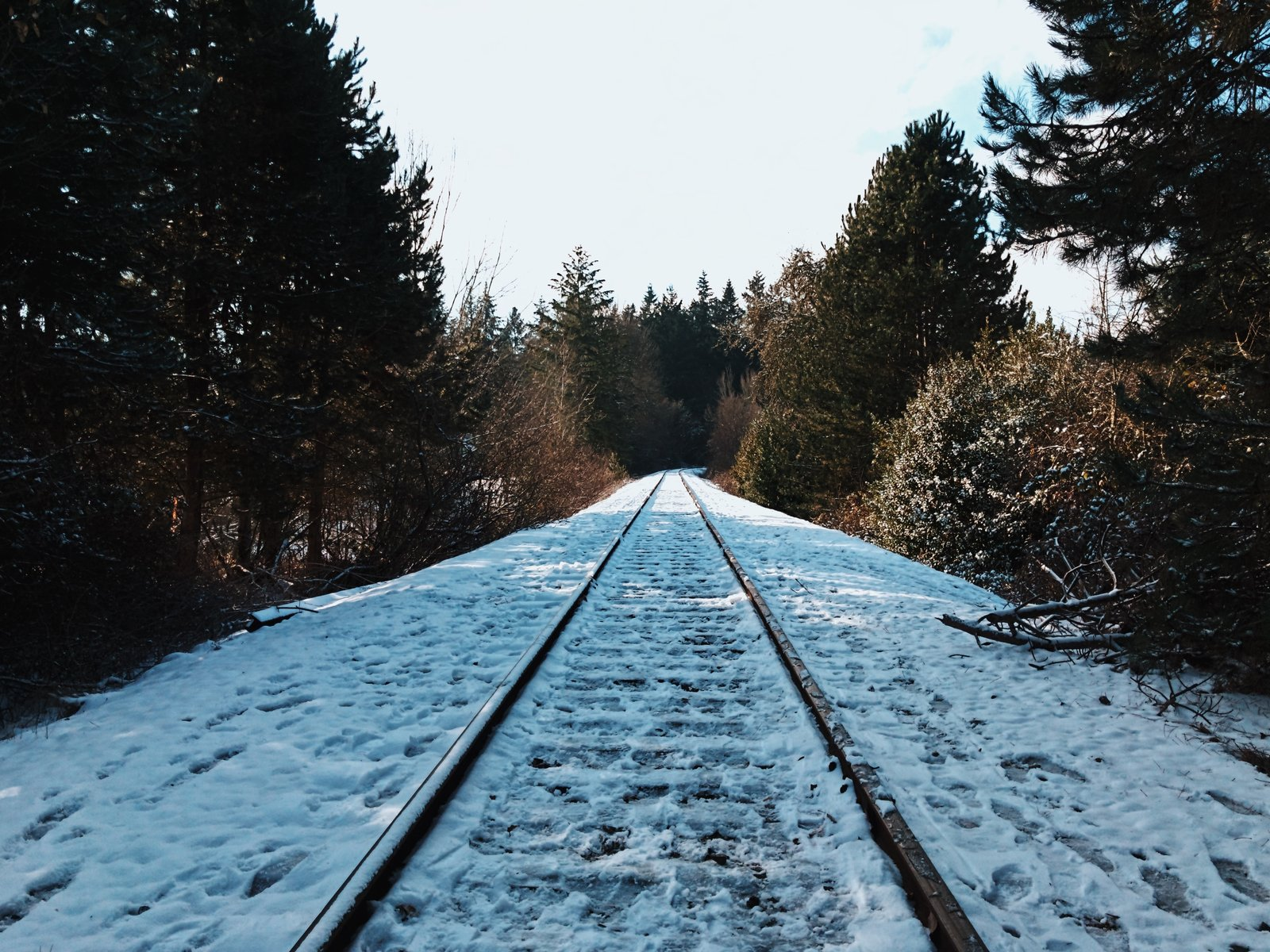 Icy foot tracks mark this snow-pelted section of railroad track.  Photo 8 of 10 in VSCO RAW/X and Topo Designs