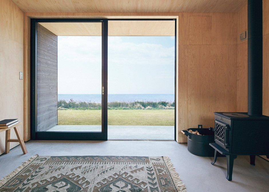 Muji Hut prefab living area with sliding glass doors