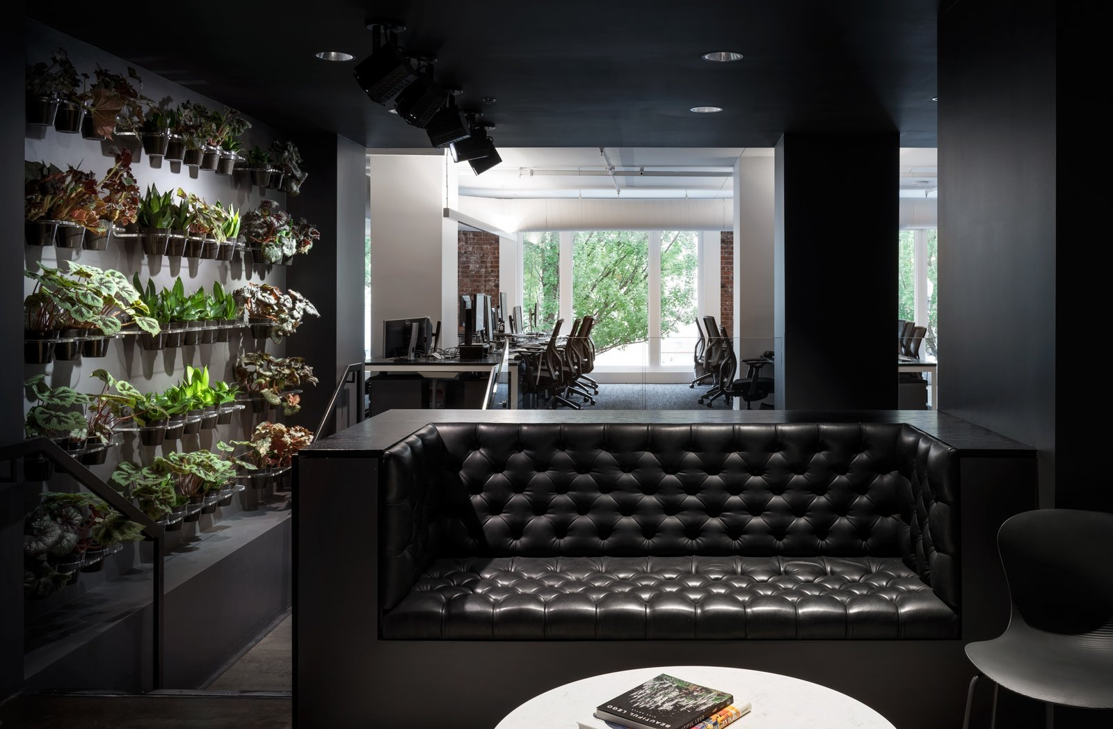 This dark lounge space with dramatic lighting is juxtaposed with a wall of carefully tended plants—hinting at the greenery that Portlanders are surrounded by year round.  Photo 5 of 12 in Step Inside Squarespace's Minimalist Portland Office
