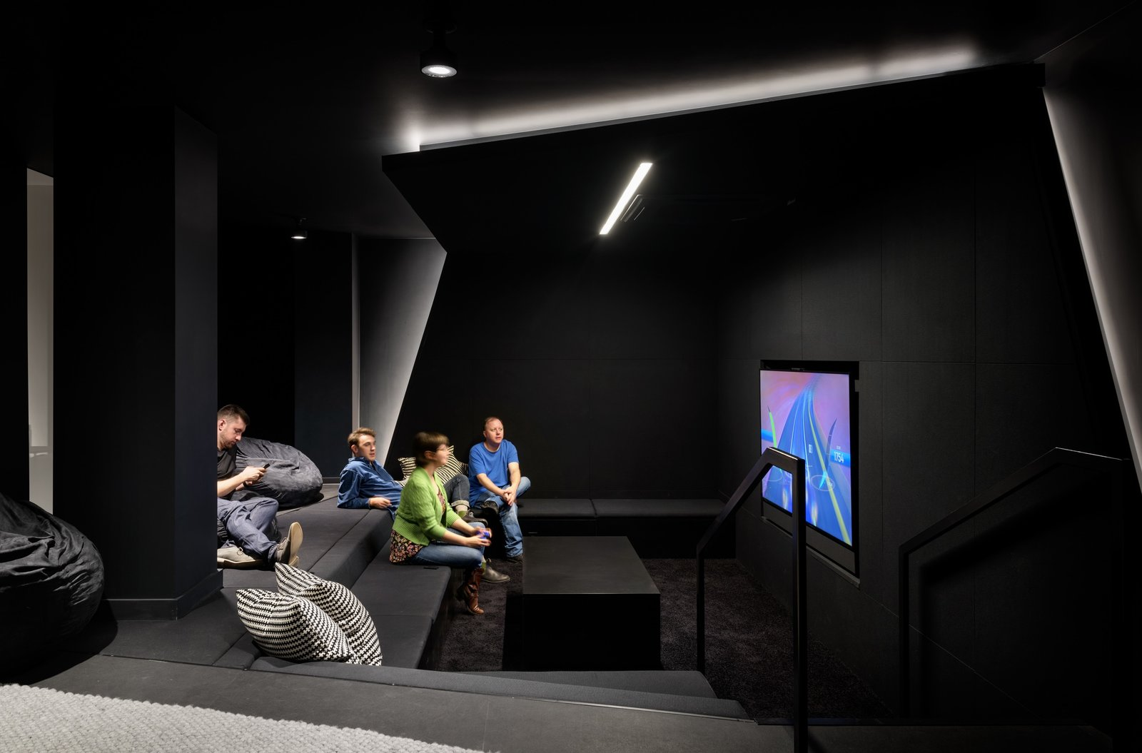 A black room with stunning geometry creates the perfect spot to chill and play some video games.  Photo 10 of 12 in Step Inside Squarespace's Minimalist Portland Office