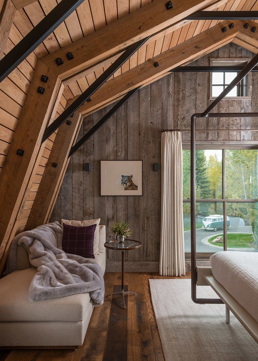 Bedroom, Rug Floor, Bed, and Medium Hardwood Floor This living/bedroom space showcases neutral tones and shades of white to contrast the continued use of natural, treated wood surfaces.  Photo 3 of 8 in A Guest Barn in Jackson, Wyoming, Fuses Modern and Rustic Elements