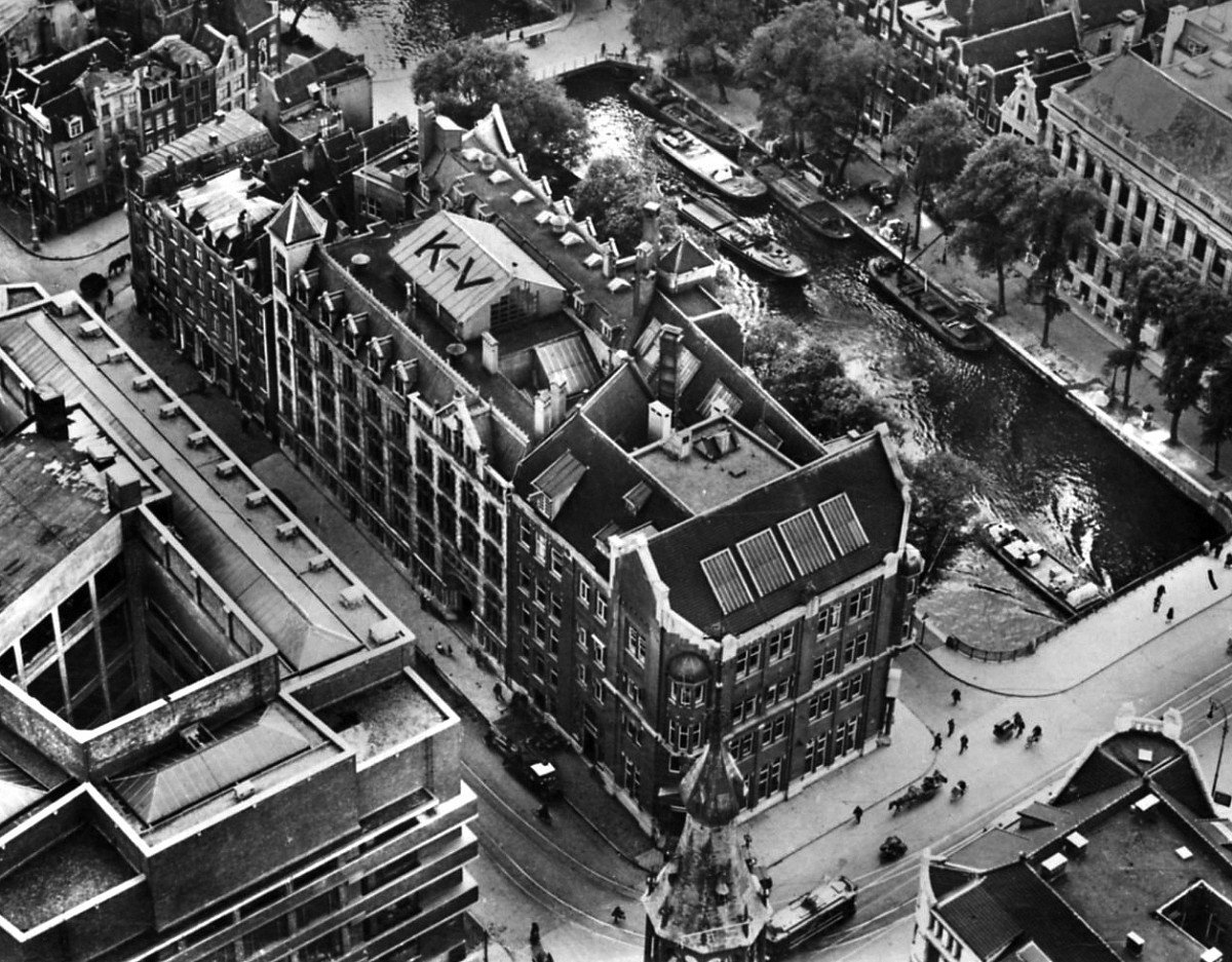 An aerial view of the bank before an expansion in 1927.  The building was originally designed by F.W.M. Poggenbeek in 1908 and was expanded in phases until 1932. The layout follows what would be expected for a bank with vaults on the ground floor and basement, a monumental bank hall on the first floor, and office space located on the upper floors.  Photo 1 of 14 in Formerly a Historic Bank, This Amsterdam Hotel Honors its Stately Roots