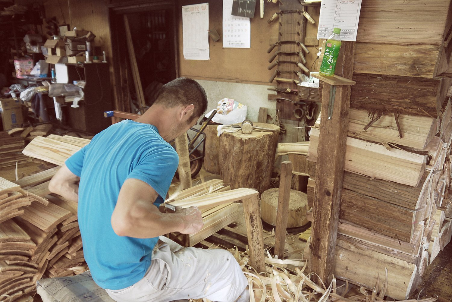 A worker is seen splitting and preparing cedar planks for use in Yoshino Cedar House.  Photo 2 of 12 in The Community-Run Cedar House by Airbnb and Go Hasegawa Welcomes Guests in Rural Japan