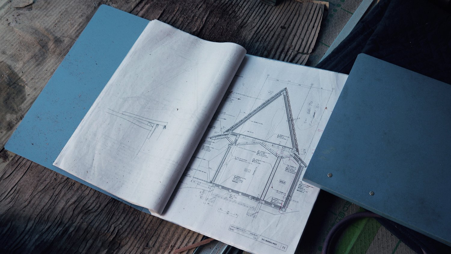 Bound books reveal the angles, measurements, and planned infrastructure for bringing the Yoshino Cedar House to life.  Photo 1 of 12 in The Community-Run Cedar House by Airbnb and Go Hasegawa Welcomes Guests in Rural Japan from Yoshino Cedar House