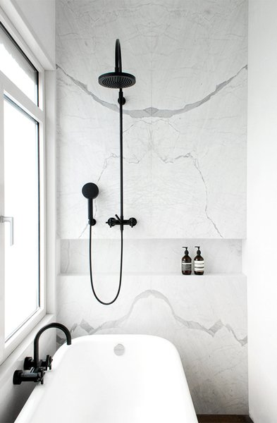 Marble wall with black shower fixtures. JVR Apartment by Dieter Vander Velpen Architects. © Patricia Goijens.  upinteriors.com/go/sph194
