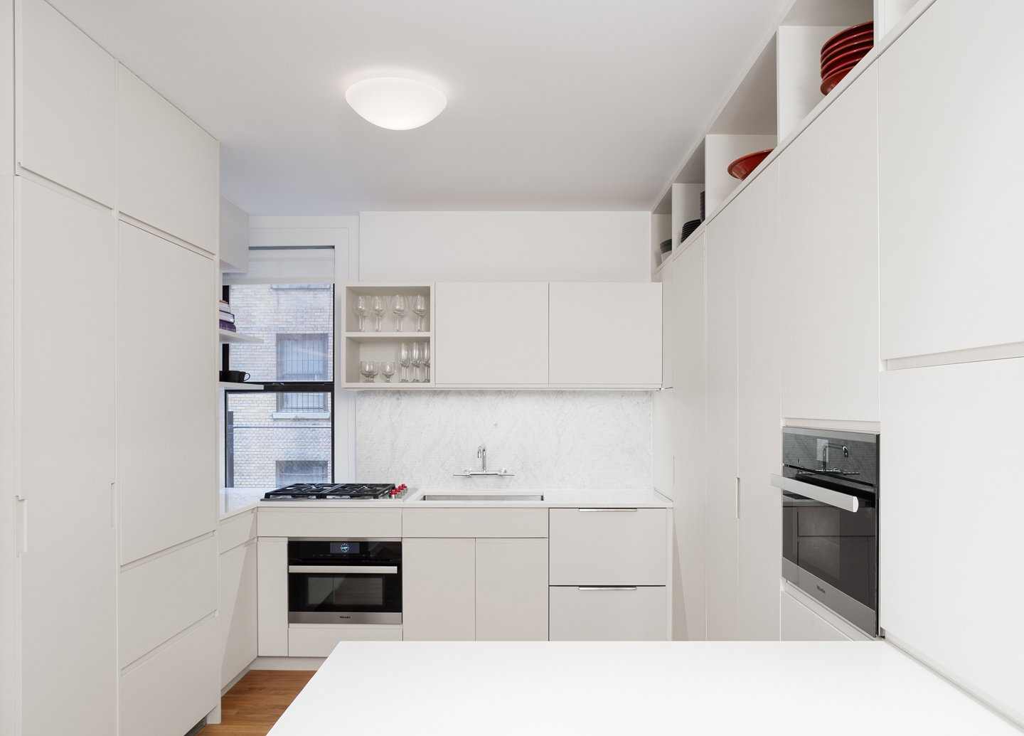 The Refrigerator, dishwasher and clothes washer are concealed behind cabinet doors and cabinets extended to the ceiling to maximize usable storage space.  Prewar Modern Upgrade by kane architecture and urban design