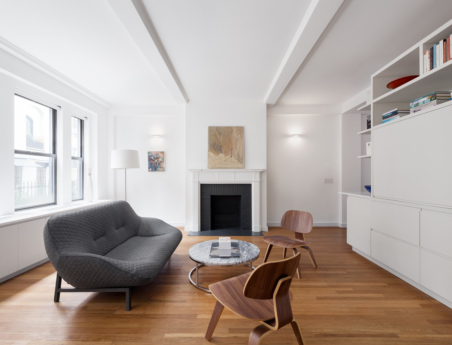 The original fireplace was restored and highlighted as the anchor to the living spaces.  Prewar Modern Upgrade by kane architecture and urban design
