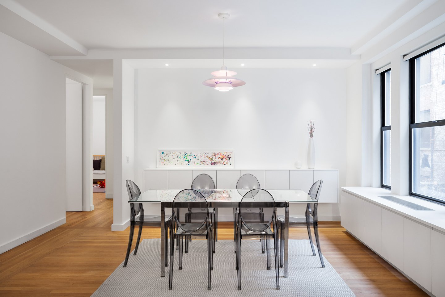 A classic pendant light, floating buffet cabinet and light washed art wall create an intimate but modern setting for dining.  Prewar Modern Upgrade by kane architecture and urban design