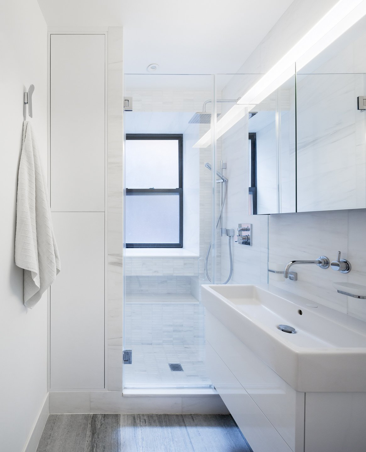 A wall mounted vanity,  glass enclosed shower and built in cabinets seek to maximizes the feeling of space within a very tight footprint.  Prewar Modern Upgrade by kane architecture and urban design