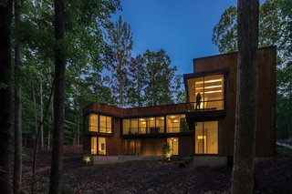 Vast expanses of floor-to-ceiling glass and cantilevered windows overlook the forest behind the house.