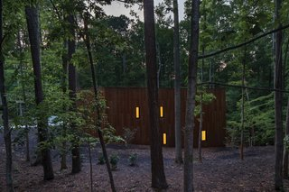 As the Corton steel blends the house into its setting, light from side windows appear like lanterns through the forest.