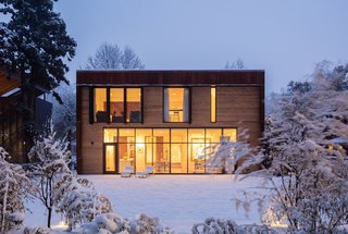 The modern addition in the snow at dusk.