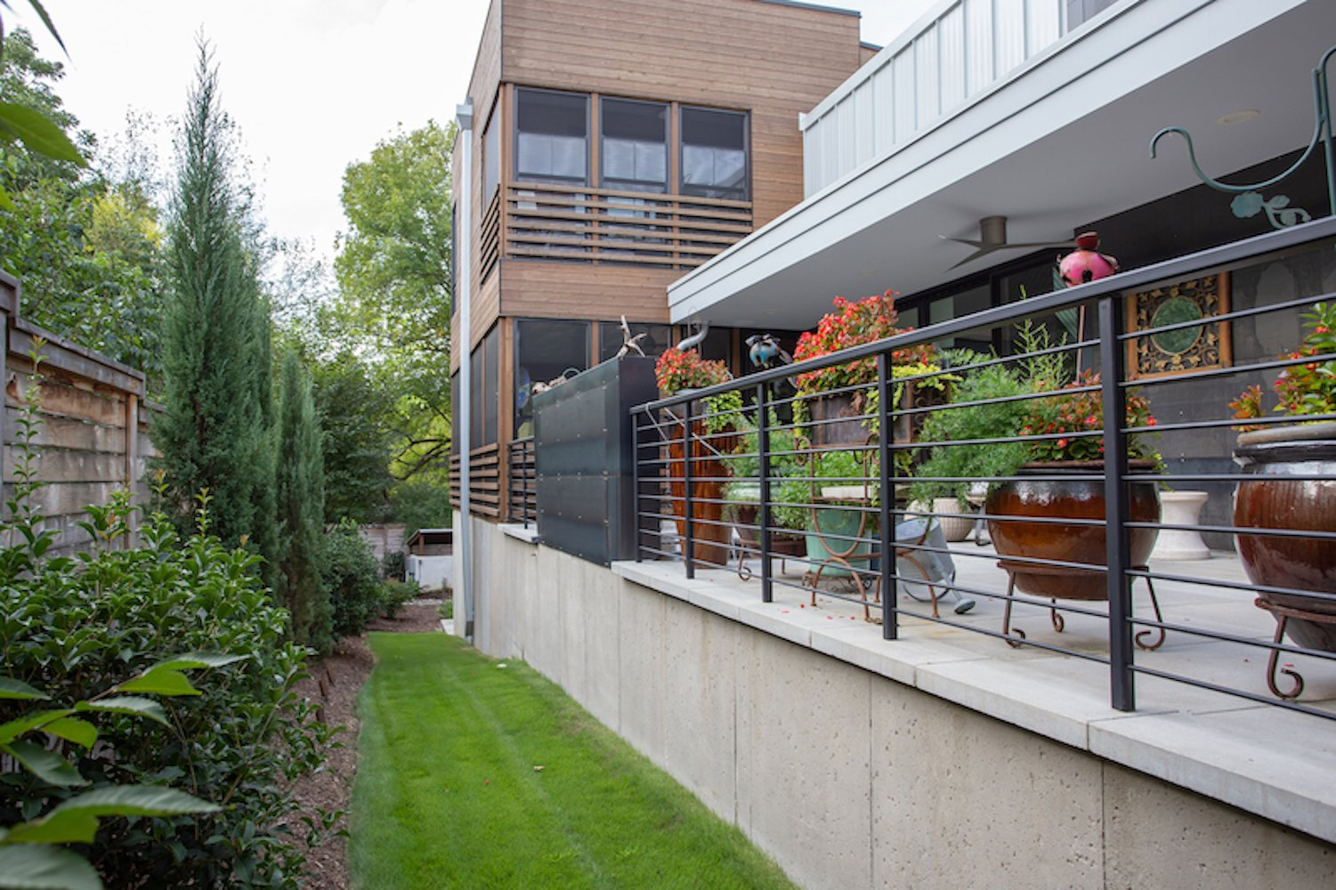 Exterior, House Building Type, Metal Siding Material, Wood Siding Material, Flat RoofLine, and Metal Roof Material The patio along one side of the house, concluding at the stacked screened porches.  The Thomas Residence