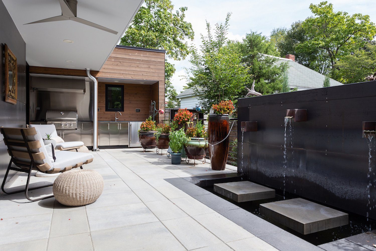 Exterior, Metal Roof Material, Flat RoofLine, Metal Siding Material, House Building Type, and Wood Siding Material The patio includes an outdoor kitchen (background) and a custom-fabricated steel water fountain.  The Thomas Residence