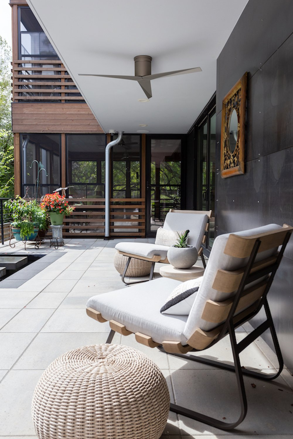 Exterior, House Building Type, Wood Siding Material, Metal Roof Material, Metal Siding Material, and Flat RoofLine The patio's back wall is clad in steel. The screened porches can be seen beyond the patio.  The Thomas Residence