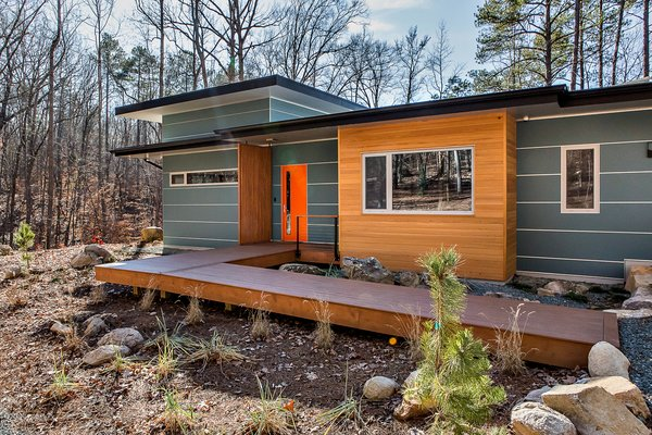 on the east entry elevation facing the approaching road strong horizontal lines in the fiber cement cladding and a cypress accent wall contribute to the houses relaxed ease in its setting a ramp provides a zero threshold age in place entry to the front do