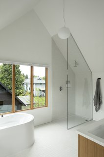 The third-floor master bathroom at Slender House enjoys a vaulted ceiling that helps create a sense of volume and spaciousness—even while showering.