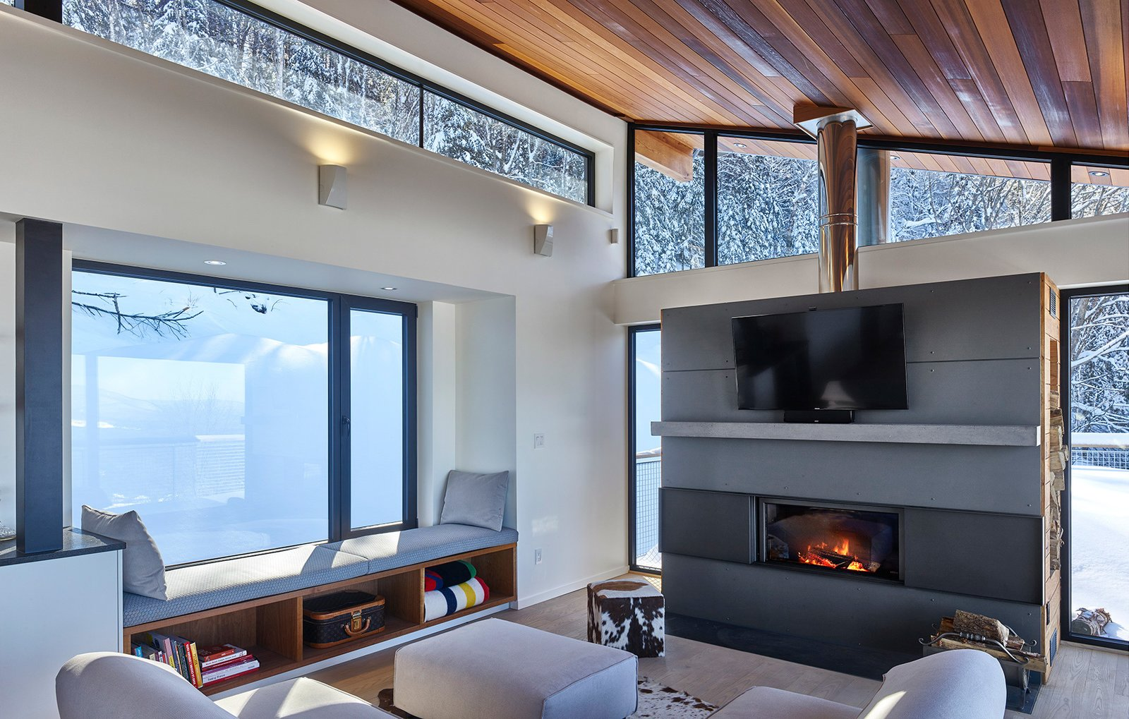Living Room, Medium Hardwood Floor, Sofa, Wall Lighting, Accent Lighting, Wood Burning Fireplace, Sectional, Light Hardwood Floor, Ottomans, Bench, and Two-Sided Fireplace Stuv fireplace and window seat with an up mountain view.  Laurentian Ski Chalet by RobitailleCurtis