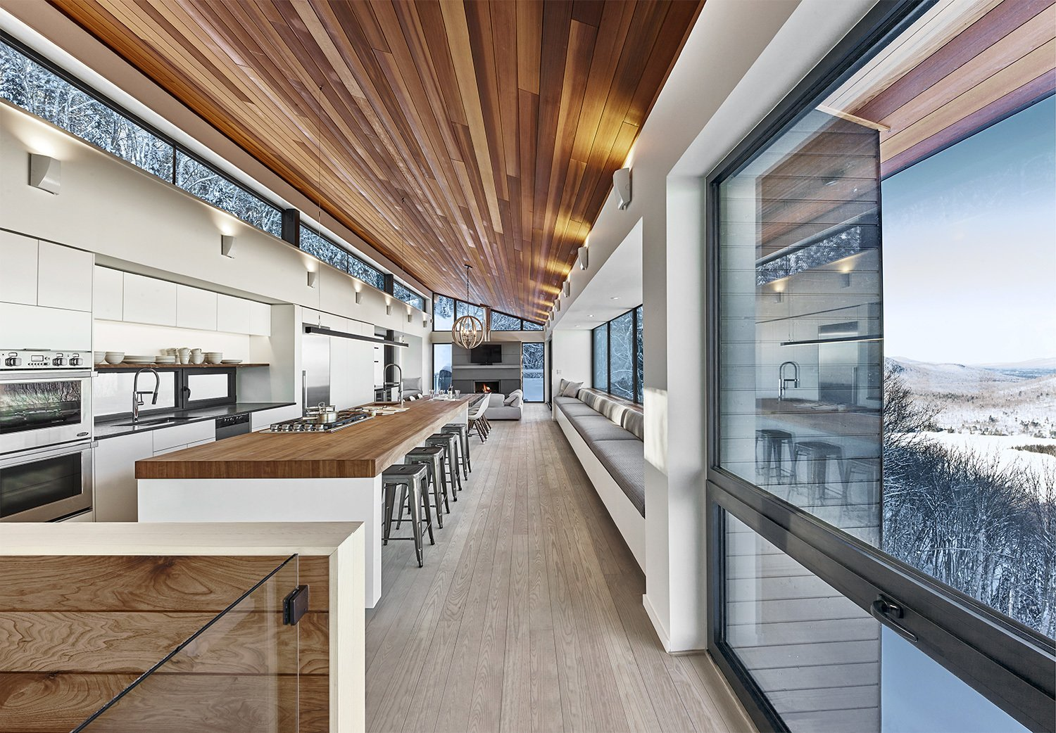 Kitchen, Medium Hardwood Floor, Wall Oven, Refrigerator, White Cabinet, Wood Counter, Ceiling Lighting, Undermount Sink, Light Hardwood Floor, Wall Lighting, Granite Counter, and Cooktops Overall view of main living space.  Laurentian Ski Chalet by RobitailleCurtis
