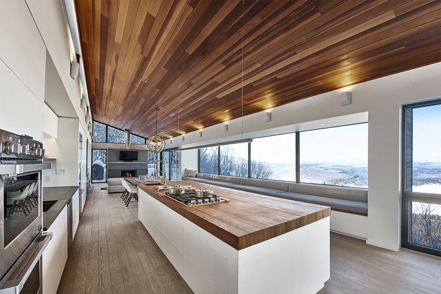 Kitchen, Medium Hardwood Floor, Ceiling Lighting, Wall Oven, Cooktops, Granite Counter, White Cabinet, Undermount Sink, Wood Counter, and Light Hardwood Floor View of kitchen and main bay window upon entry into primary living space.  Laurentian Ski Chalet by RobitailleCurtis