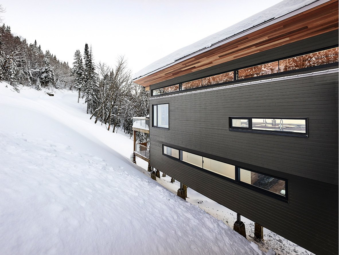 Exterior, Wood Siding Material, Metal Roof Material, Shed RoofLine, Cabin Building Type, and House Building Type Partial view of main facade from entry bridge.  Laurentian Ski Chalet by RobitailleCurtis
