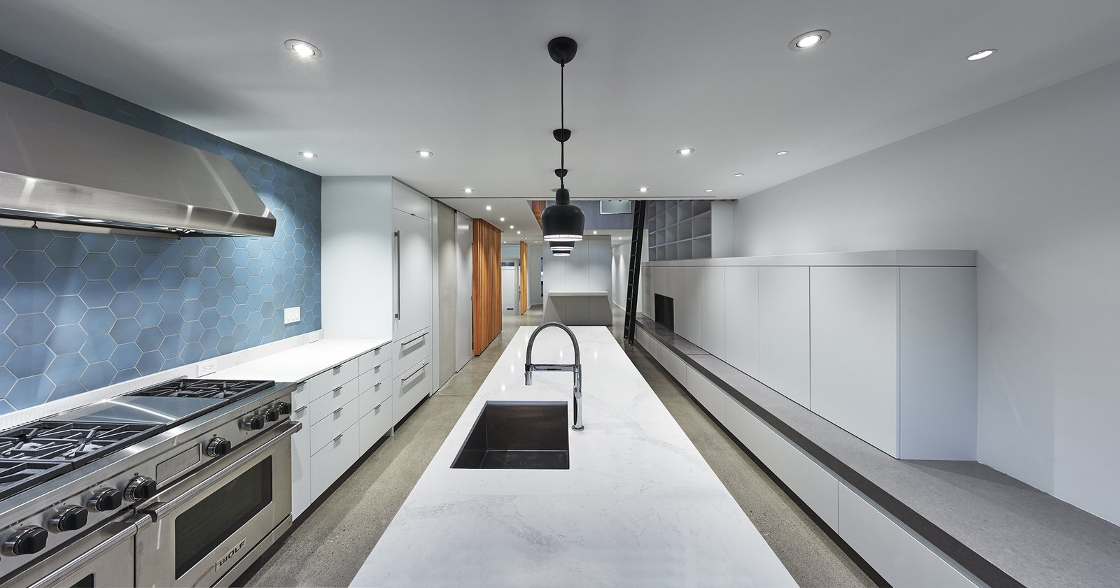 Kitchen, White Cabinet, Concrete Floor, Ceramic Tile Backsplashe, Pendant Lighting, Recessed Lighting, Range Hood, Range, Undermount Sink, and Marble Counter Alvar Aalto's A330 pendant fixtures above the kitchen island.  Atrium Townhome by RobitailleCurtis