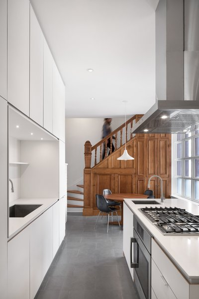 The kitchen in the Winchester Residence features plywood cabinets with white Fenix cladding. RobitailleCurtis moved the rear service stair forward into the kitchen to allow a new stair to the basement to be concealed beneath it.