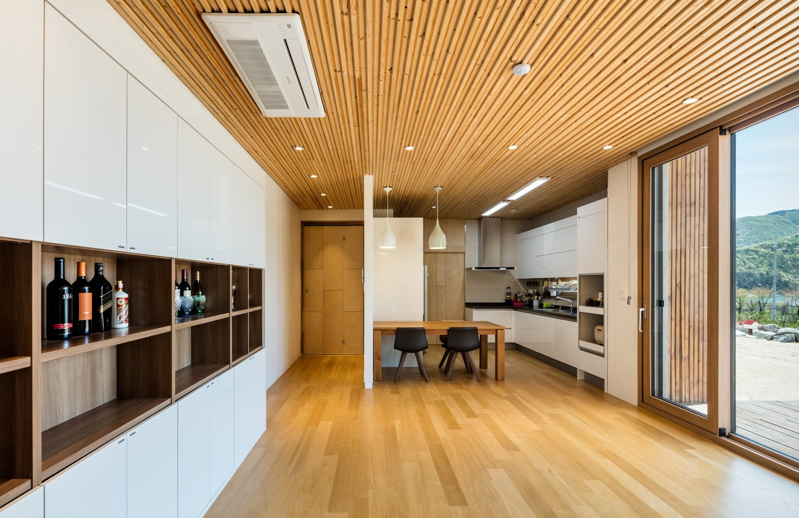 Dining Room, Table, Ceiling Lighting, and Medium Hardwood Floor dining & kitchen  Apple Farm House by 2m2 architects