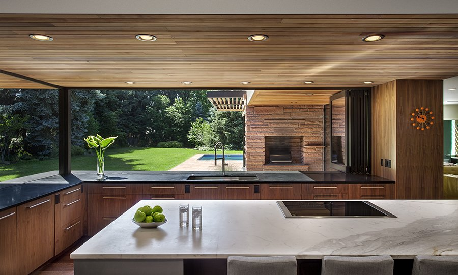 The Kemps wanted to emulate a European-style kitchen that would be minimal in appearance, but highly functional. Their induction cooktop is centered in an island of white Calcutta marble. Custom base cabinets at the island have a cool gray automobile paint finish. The perimeter countertops are fabricated from absolute black granite while the walnut base cabinets continue the classic mid-century vibe. A sleek folding panel window system allows the kitchen to have full exposure to the exterior.  Photo 3 of 5 in Ranch Reprise