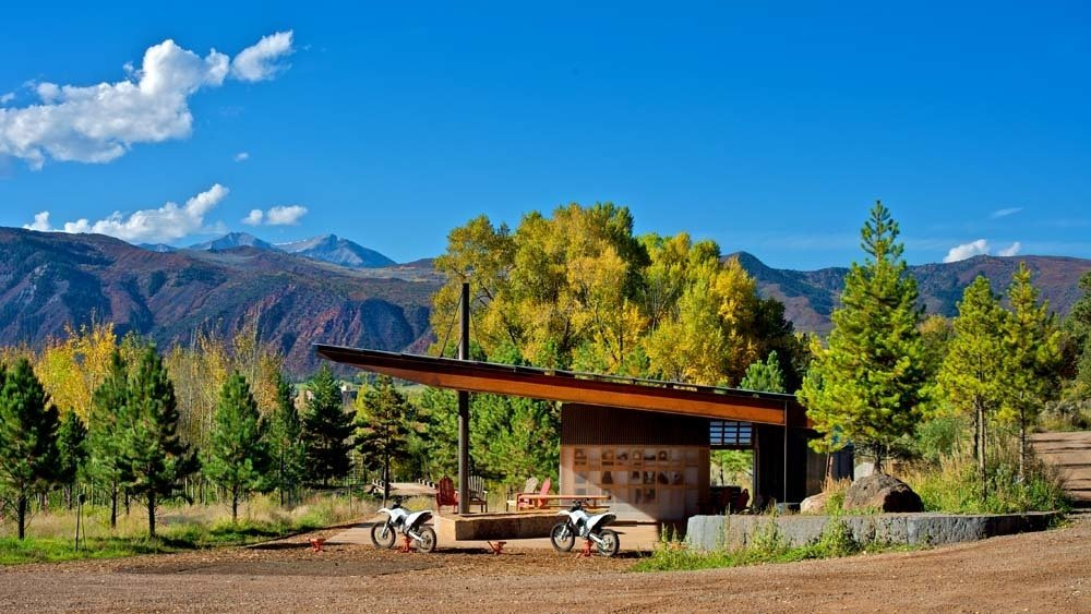Outdoor, Field, Trees, and Shrubs Black Shack Architects designed a modern motocross shelter in an elemental way. When Glenn Rappaport's long-time client approached him to design a shade structure along a private motocross track in El Jebel, Colorado, he was inspired by the elemental nature of the project. The family, with three teenage boys, wanted a shelter that would provide protection from the elements, a small changing area, restroom, fire pit, and storage for cold drinks.  Photo 16 of 16 in 16 Inviting Countryside Cabins from Rock, Paper, Scissors