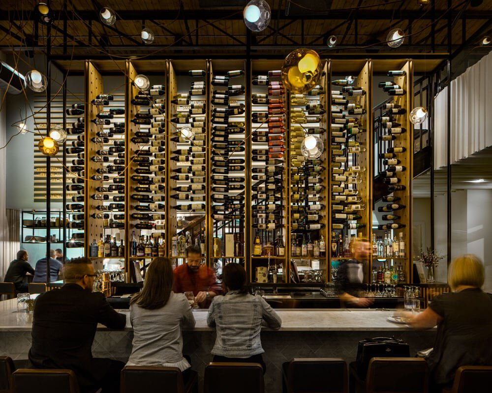 The two story wine rack at Il Posto serves as a focal point within the space. It also functions as a screen between diners and the kitchen. Guests are afforded multiple views of the towering piece as the stair to the mezzanine slides behind the rack and moves through the space.  Photo 4 of 8 in Illuminating Atmosphere With 111 Bocci Lights