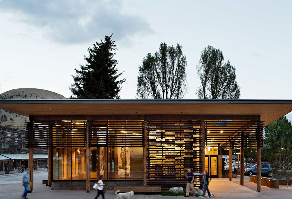 HOME RANCH – Jackson Hole's Home Ranch Welcome Center rests at the northern entrance to historic downtown, where it provides visitor information about opportunities for discovery in the town of Jackson and the surrounding National Parks. Program components are expressed individually, as an opaque concrete enclosure houses restroom facilities, and a gallery on the public corner is light-filled and transparent. Inspiration for the project was taken from the regional abundance of porches, which provide welcome, shelter, and entry for natives and tourists alike. Carney Logan Burke also worked with a local artist to create Jackson's first publicly funded art project, Strands. The work is made of glass bricks representing bison and bear DNA, and those bricks are integrated into the building's solar shade screens. The Home Ranch Welcome Center won three AIA Awards, including a 2014 Award of Excellence from the Wyoming Chapter. Photo by Paul Warchol.  Photo 6 of 16 in Naturally Modern