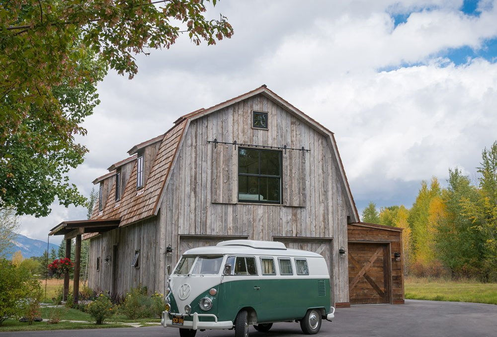 """THE BARN – What looks from the exterior like a possible renovation project was actually built from the ground up to resemble the traditional barn form, while also incorporating modern and contemporary elements. Said Eric Logan, """"In keeping with the rest of the architecture of the compound of buildings there, this needed to be a traditional take on architecture, with the old wood, the gambrel roof form, and the dormers."""" The interior expression, on the other hand, is light and airy, with an exposed structural system and floor-to-ceiling glass walls on the upper level. """"You ascend the stairway and get this beautiful view of the structure and the contrast of light and dark in the ceiling. Then there's this incredible exposure from 15 feet off the deck, and the dramatic view of the Teton range beyond."""" Photos by Audrey Hall.  Photo 5 of 16 in Guide to 7 Main Types of Roofs and What You Need to Know About Them from Naturally Modern"""
