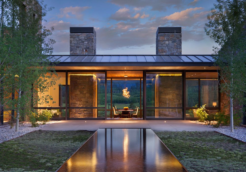 CRESCENT H – Situated on top of a sloping knoll and an aspen grove, this home was sited to capture panoramic mountain views and create a dramatic arrival sequence. The program is arranged in separate building forms to cultivate intimacy while maximizing exposure. Movement is choreographed to contrast solid characteristics with void, creating pockets of shelter and outdoor connections. The roof protecting the kitchen pavilion, along with the kitchen and dining rooms, lays across an east-west axis to take full advantage of the scenery. Sedimentary stone from a nearby quarry mimics the natural landscape, with clear vertical grain cedar siding to break up the pattern and add warmth. Photo by Gibeon Photography.  Photo 14 of 16 in Naturally Modern