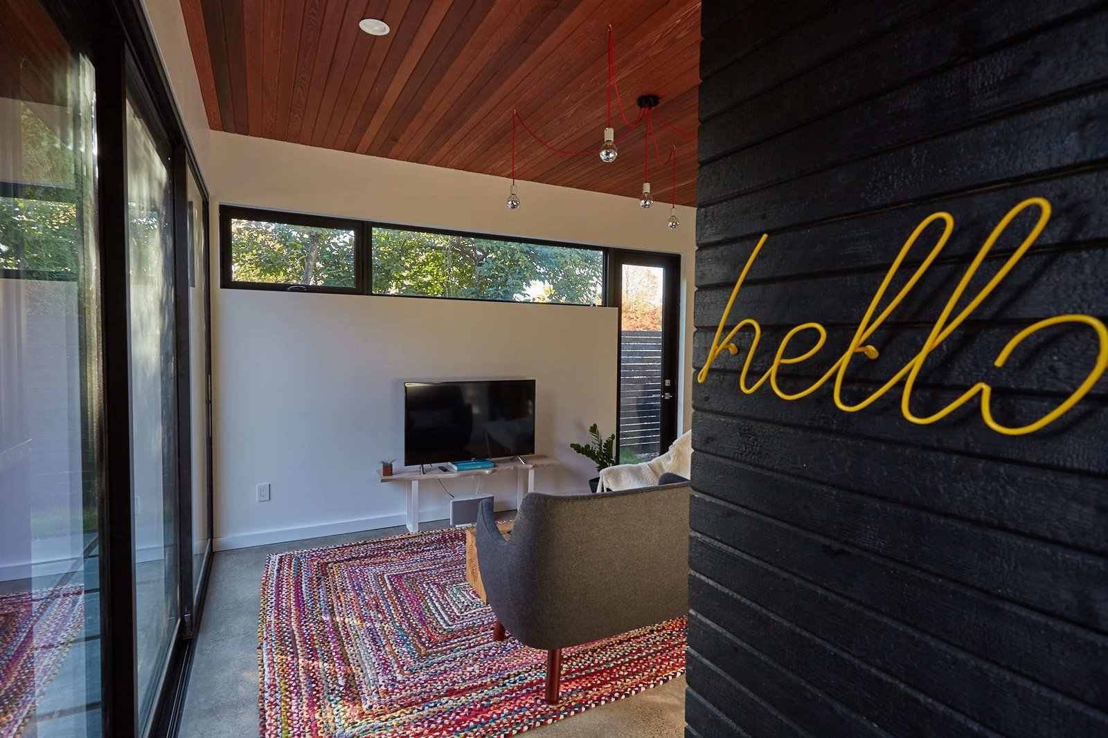 """Living Room, Recessed Lighting, Sofa, Ceiling Lighting, and Concrete Floor The """"hello"""" coat rack pops against the charred cedar wall  The Mansfield Frogner House"""