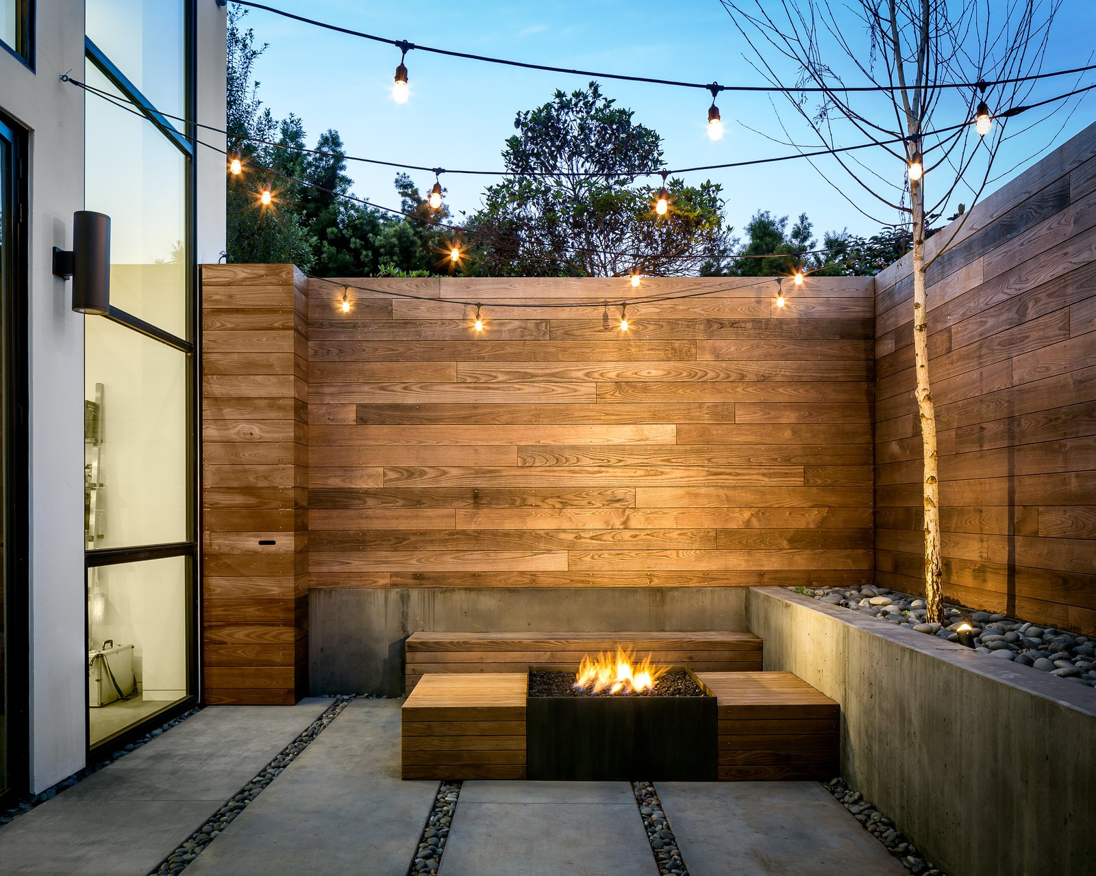 Outdoor, Small Patio, Porch, Deck, Walkways, Shrubs, Concrete Patio, Porch, Deck, Landscape Lighting, Hardscapes, Wood Fences, Wall, Raised Planters, Trees, Back Yard, and Hanging Lighting Back patio  Photo 17 of 19 in 18 Modern Fireplaces and Fire Pits to Inspire Outdoor Living from SF House-Tech-Art-Play