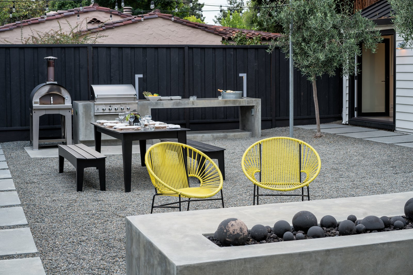 The area between the outdoor kitchen and fireplace can be rearranged to fit the moment  Refreshing Bungalow by Randy Thueme Design