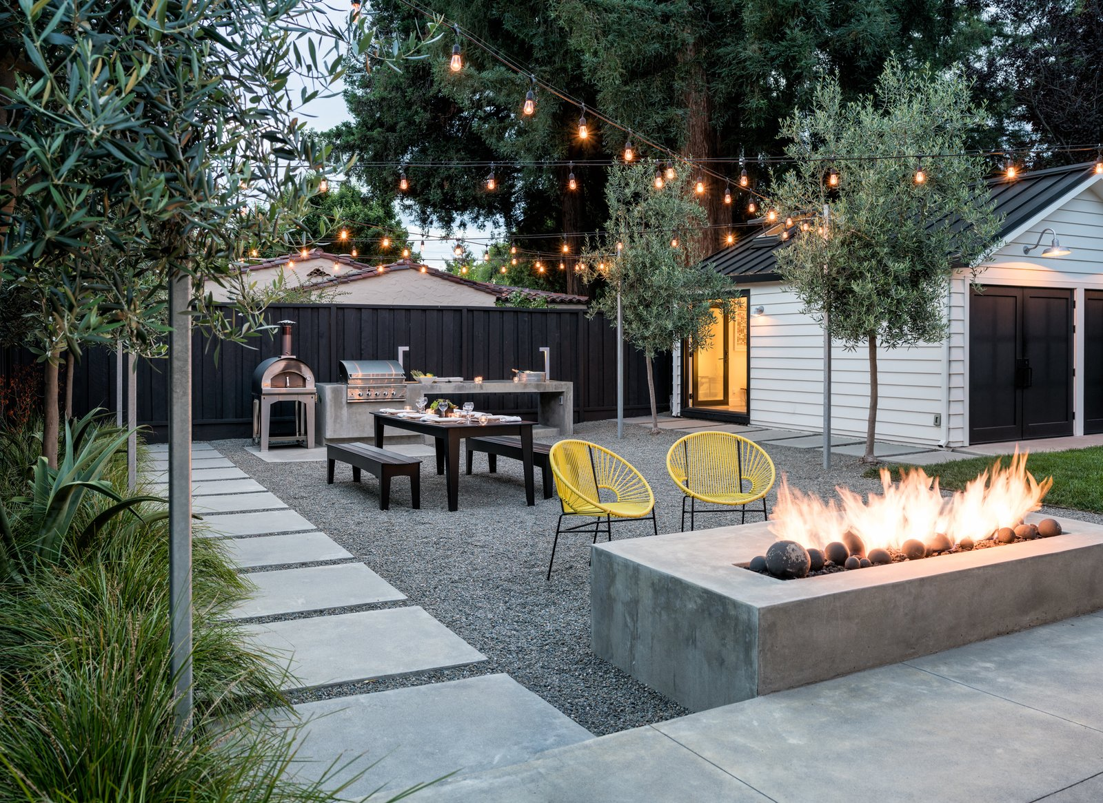 At dusk the fire and lighting extend the hours of use  Refreshing Bungalow by Randy Thueme Design