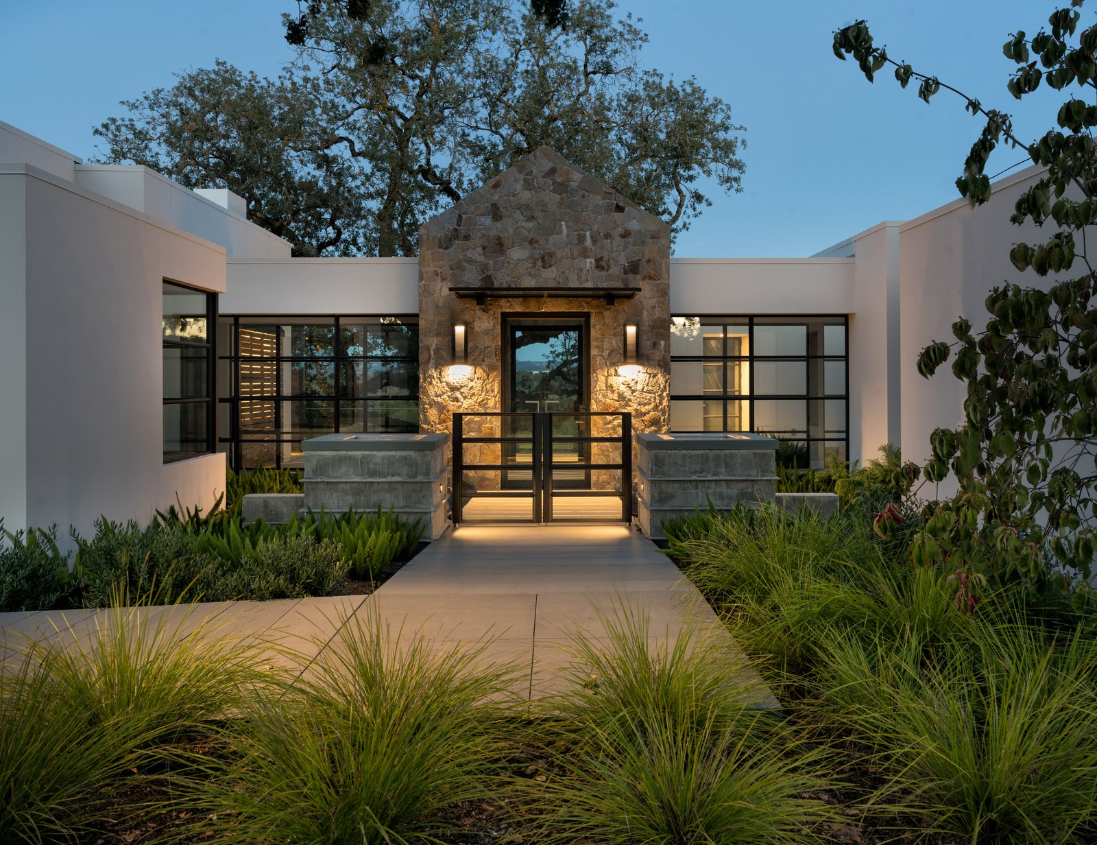 Outdoor, Trees, Grass, Shrubs, Landscape Lighting, Concrete Patio, Porch, Deck, Hardscapes, Back Yard, and Garden A warmly welcoming entrance to the home  Hilltop Haven by Randy Thueme Design