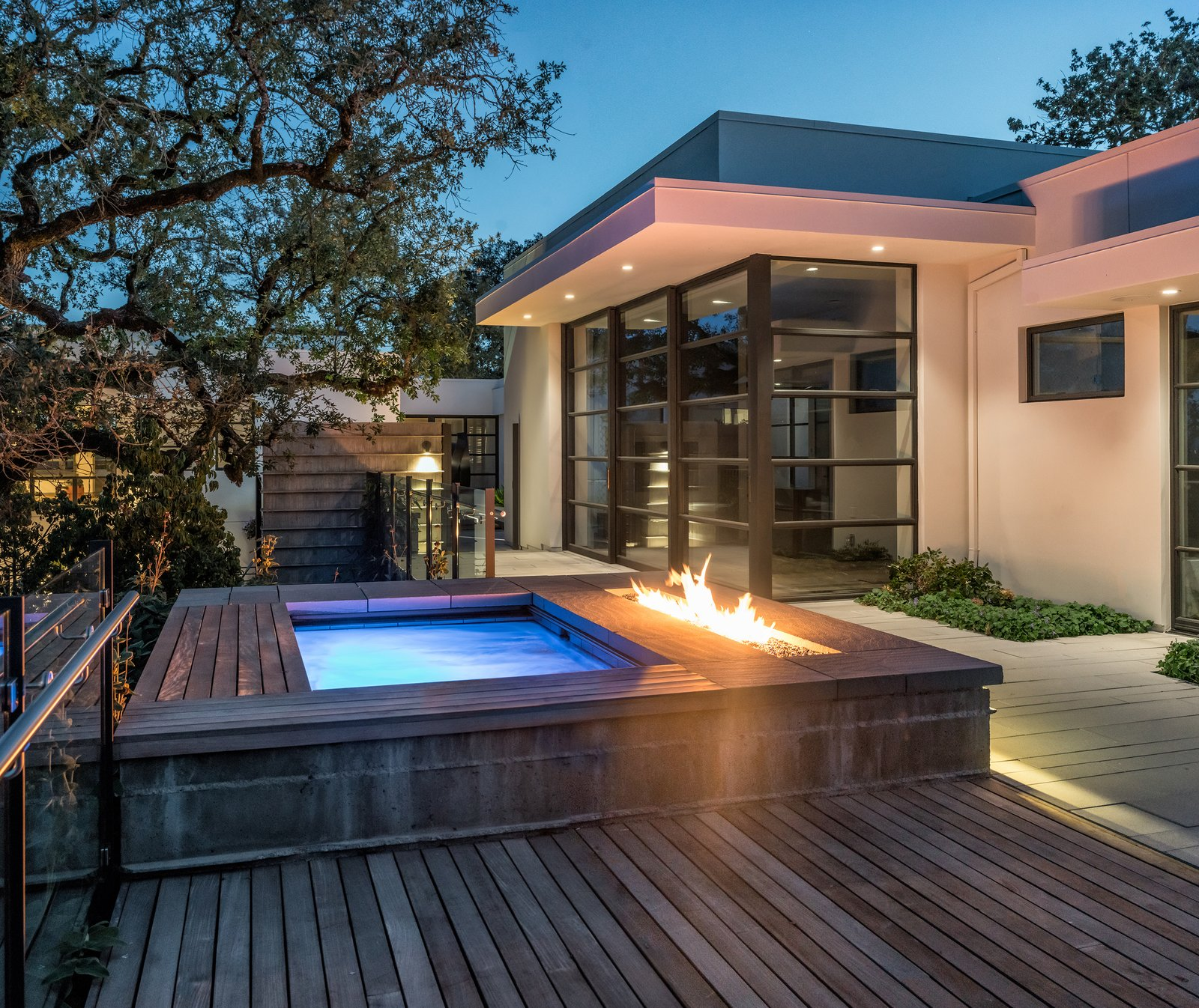 Outdoor, Wood Patio, Porch, Deck, Small Pools, Tubs, Shower, Concrete Patio, Porch, Deck, Trees, Shrubs, Small Patio, Porch, Deck, Hardscapes, Back Yard, and Landscape Lighting Lighted spa and fire feature at twilight  Hilltop Haven by Randy Thueme Design