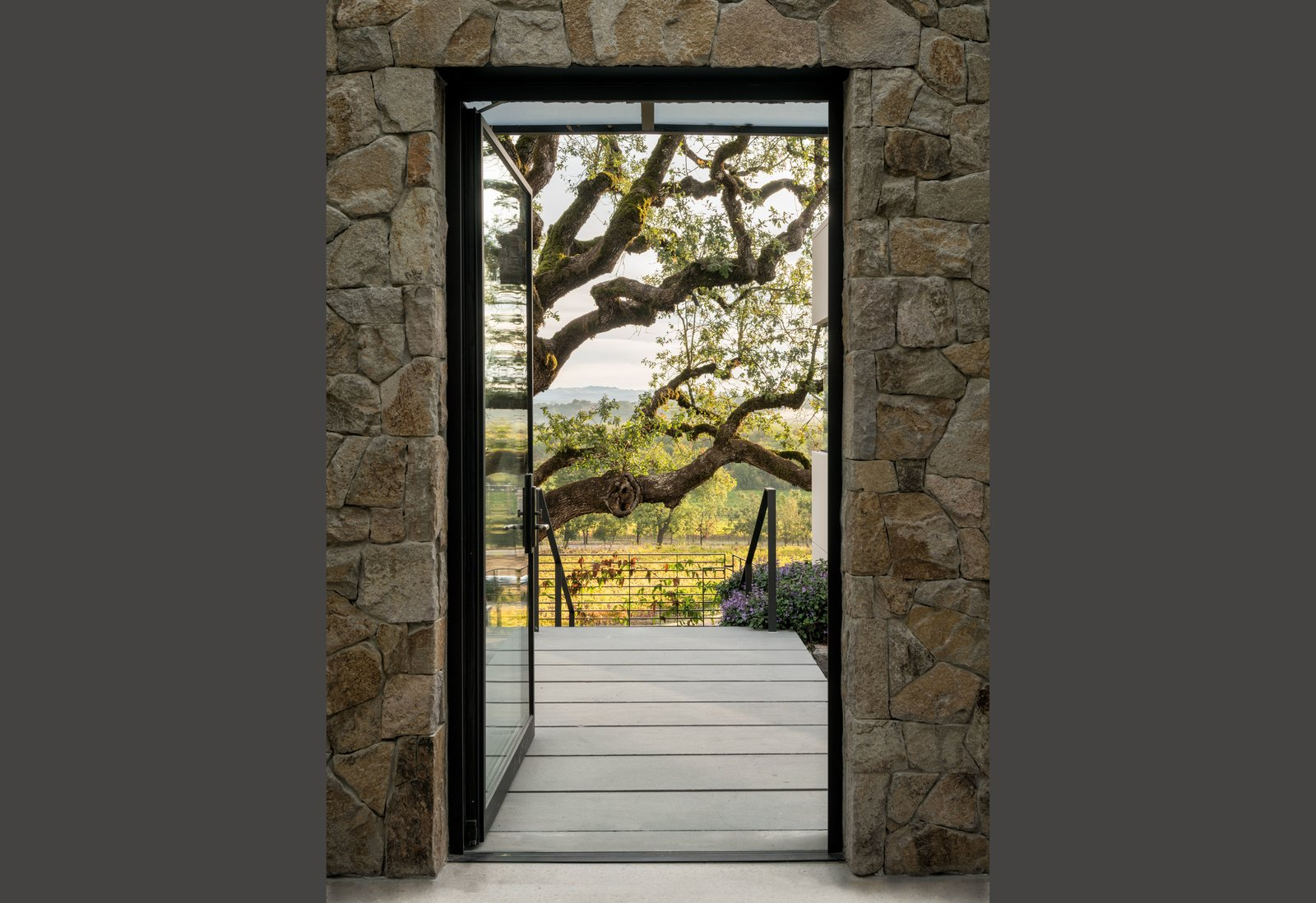 Outdoor, Trees, Shrubs, Gardens, Front Yard, Hardscapes, Stone Patio, Porch, Deck, and Concrete Patio, Porch, Deck View through entry pavilion to Oak and vineyards  Hilltop Haven by Randy Thueme Design