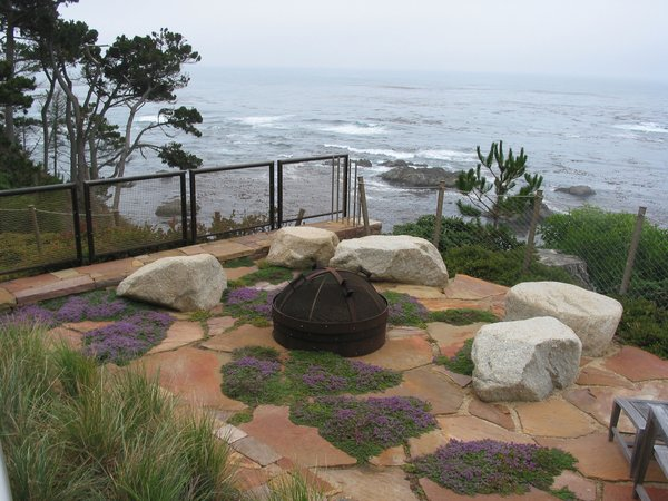 Elements in the landscape such as wall benches, stairway landings, a belvedere overlook and the seat rocks at the fire pit area shown here provide opportunities to stop and take in the view.