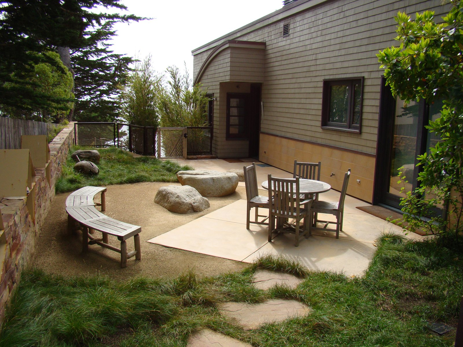 Outdoor, Side Yard, Garden, Trees, Shrubs, Gardens, Grass, Hardscapes, Boulders, Decomposed Granite, Concrete, and Stone A quiet, sheltered outdoor dining area  Outdoor Side Yard Concrete Decomposed Granite Hardscapes Photos from On the Edge
